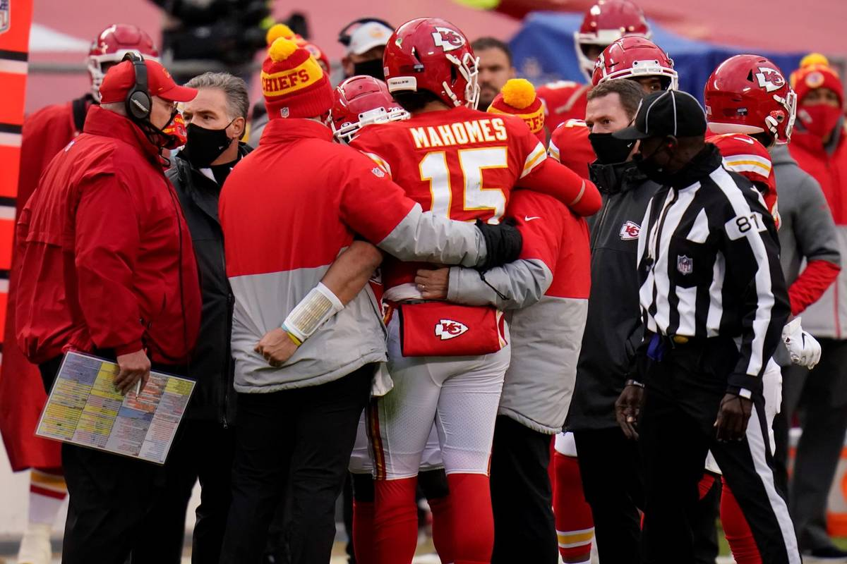 Kansas City Chiefs quarterback Patrick Mahomes (15) is helped off the field after getting injur ...