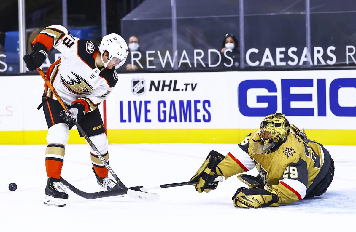 Golden Knights goaltender Marc-Andre Fleury (29) knocks the puck away from Anaheim Ducks center ...