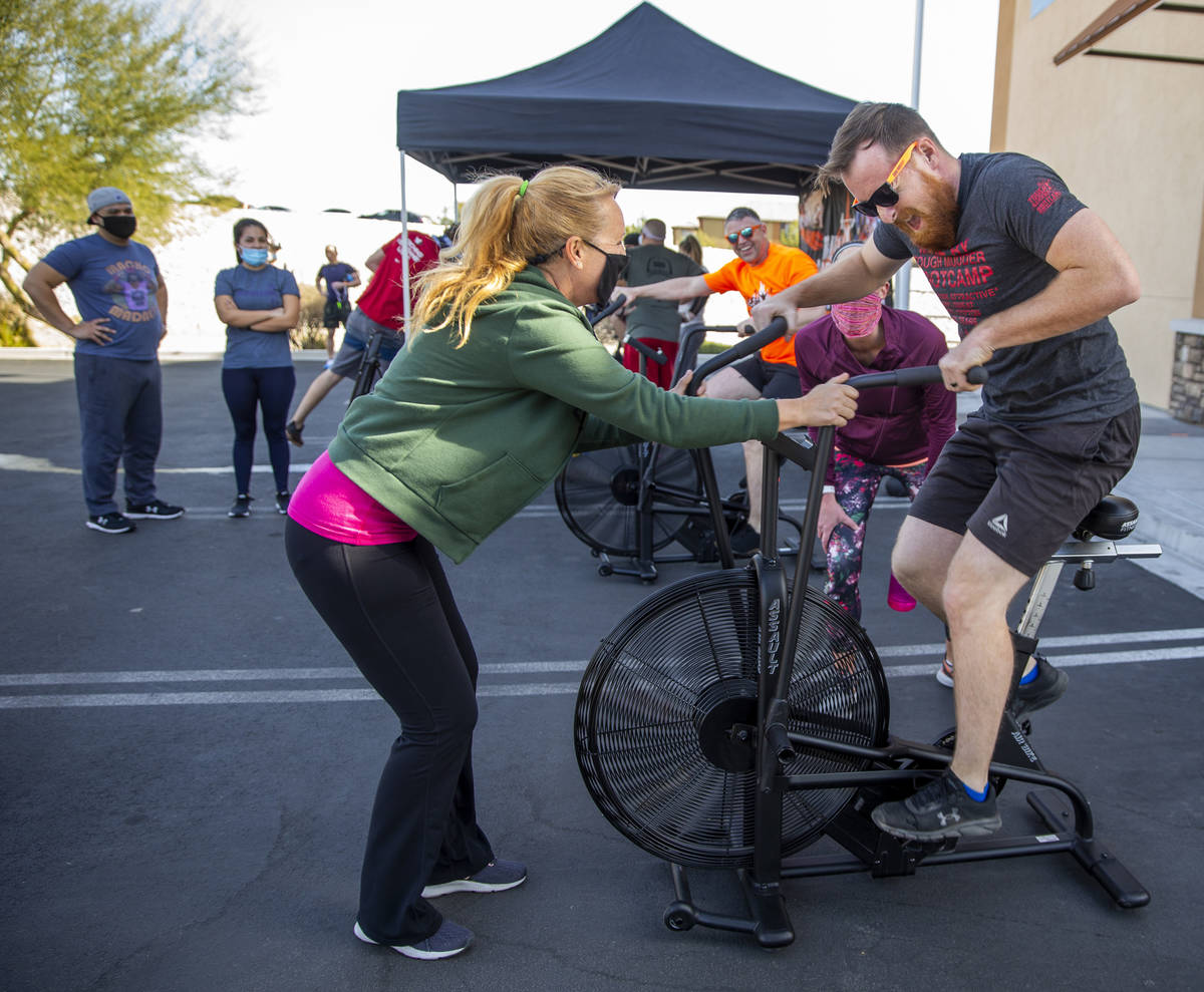 Patrick Lucas, left, grinds out some miles with an assist from Bobbie Martin as Tough Mudder Bo ...