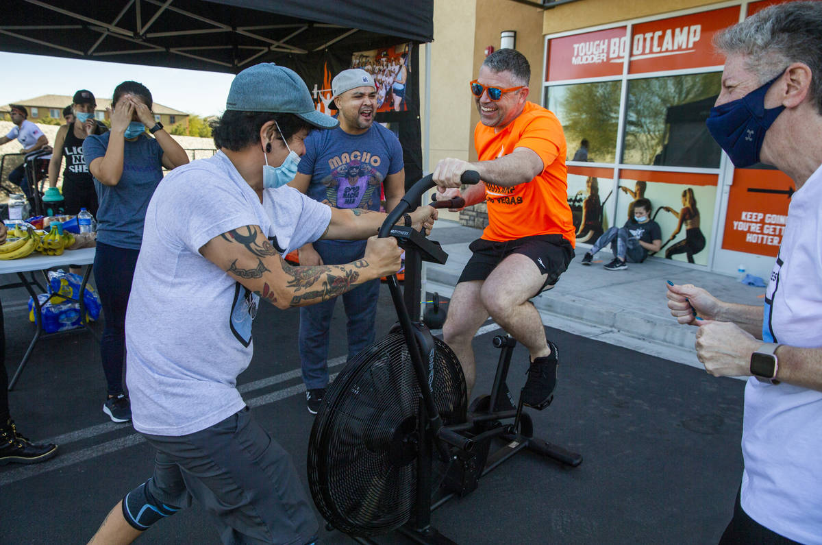 Co-owner Cory Drumright, center, is pumped up by Ron Bondoc,left, and others as he pedals some ...