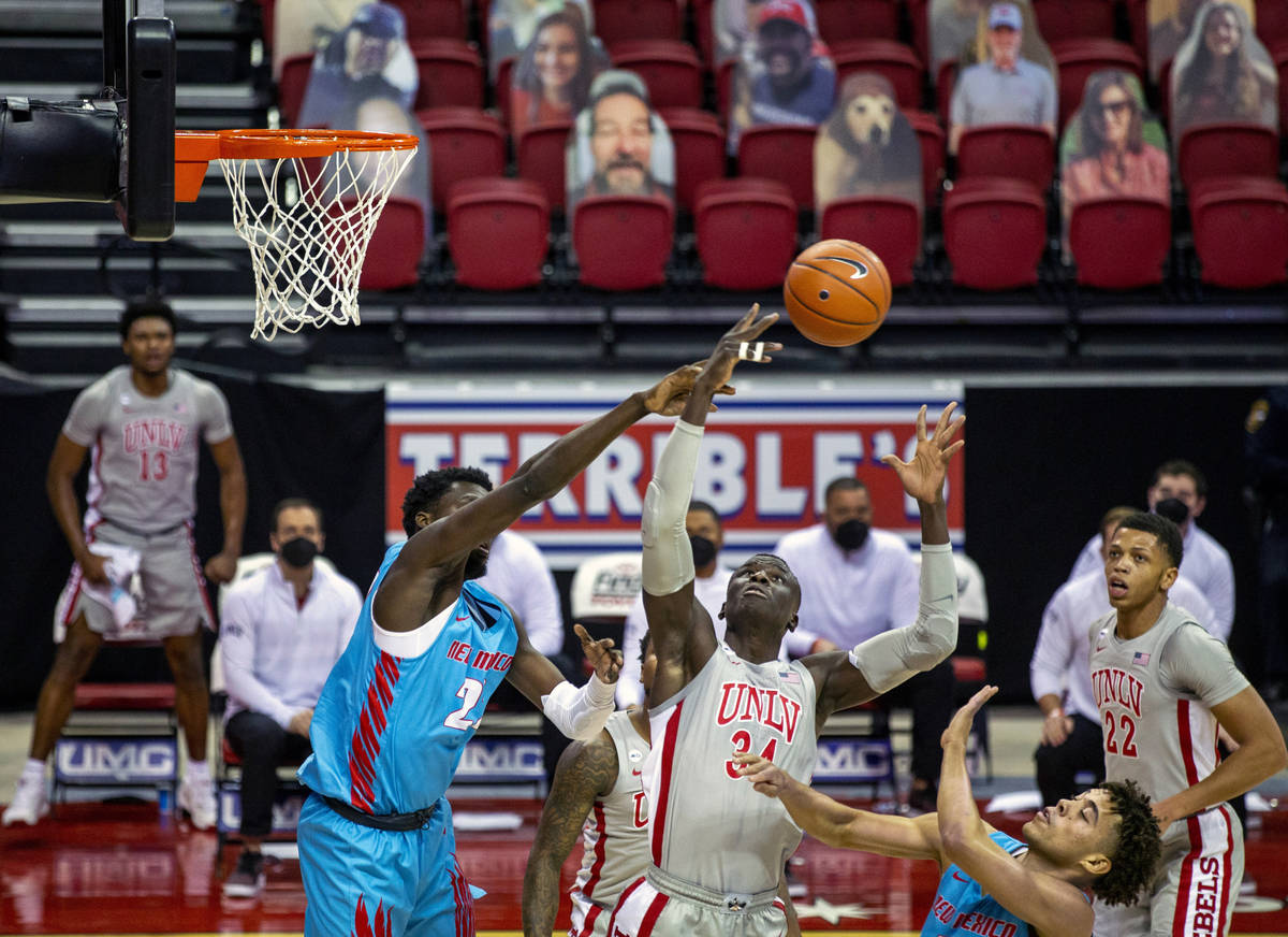 UNLV Rebels forward Cheikh Mbacke Diong (34) deflects a loose ball from New Mexico Lobos forwar ...