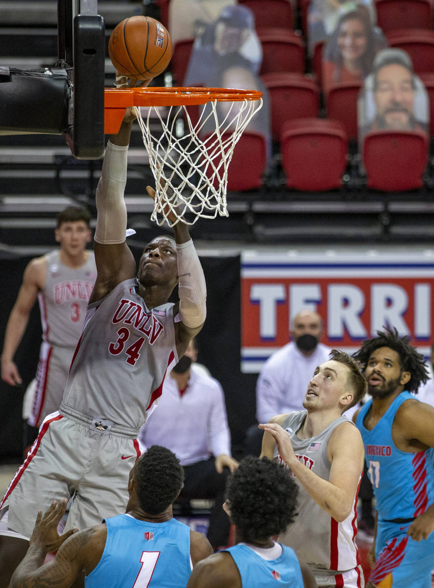 UNLV Rebels forward Cheikh Mbacke Diong (34) readies for a dunk over New Mexico Lobos forward B ...