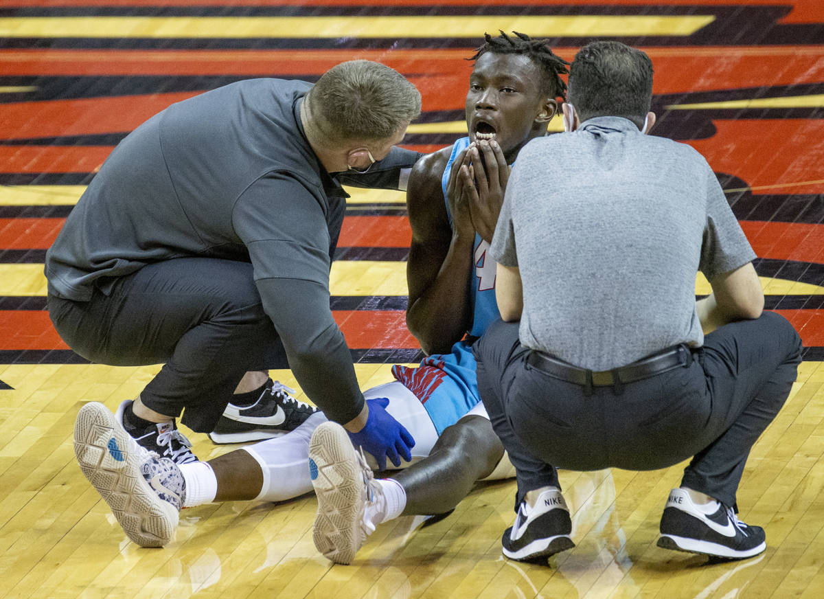 New Mexico Lobos guard Emmanuel Kuac (4) sits dazed on the court after colliding with UNLV Rebe ...