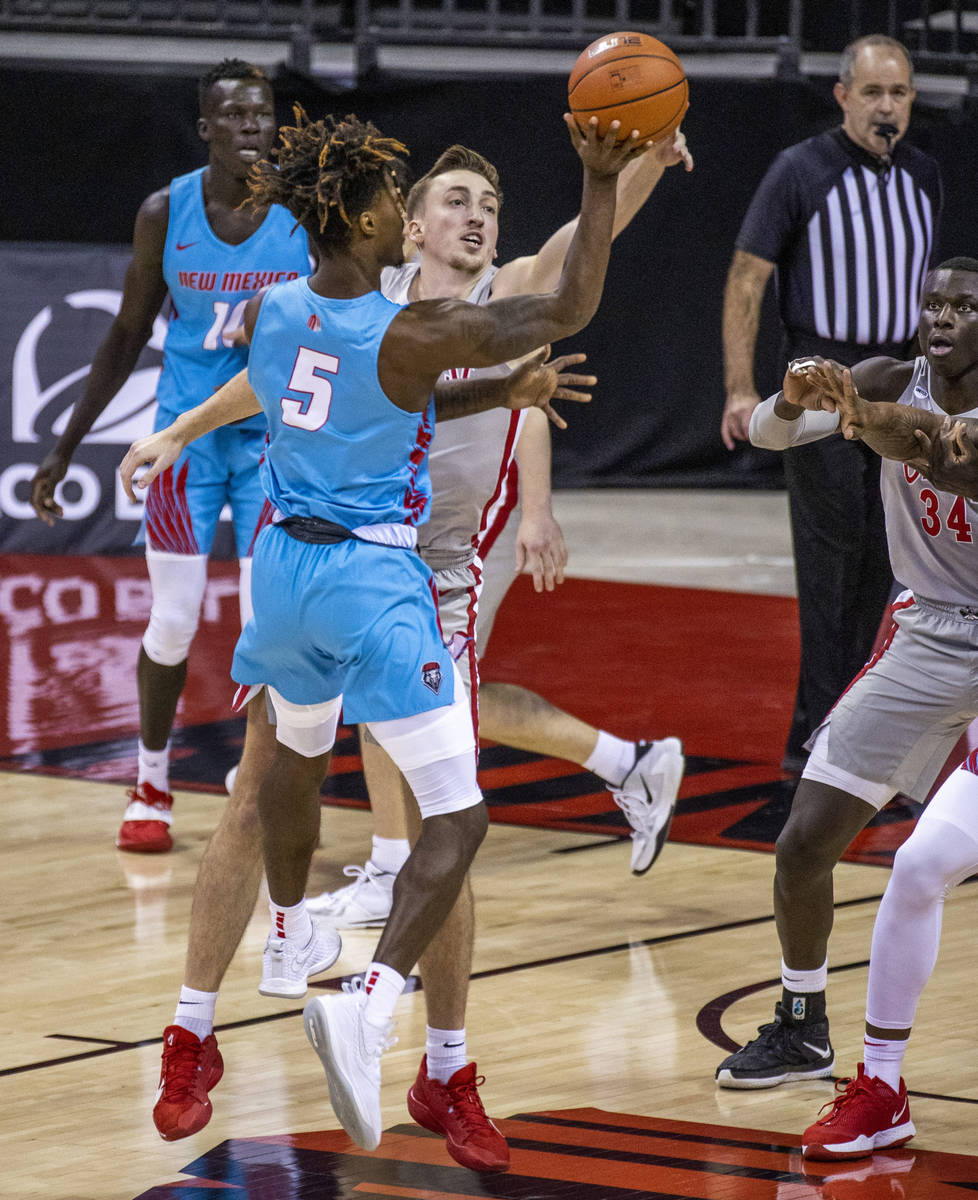 New Mexico Lobos forward Rod Brown (5) has a shot rejected by UNLV Rebels forward Moses Wood (1 ...