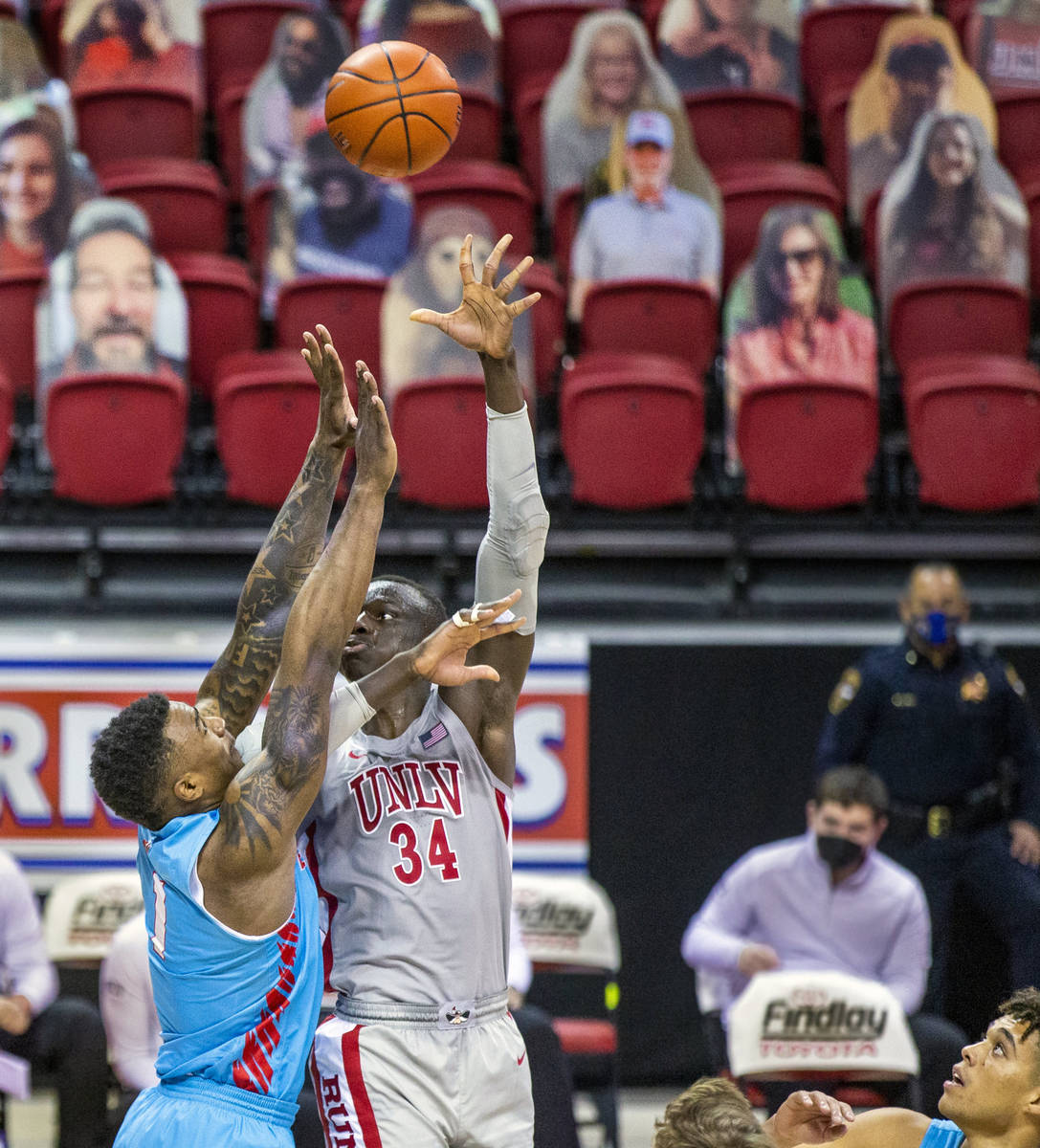 UNLV Rebels forward Cheikh Mbacke Diong (34) gets off a hook shot over New Mexico Lobos forward ...