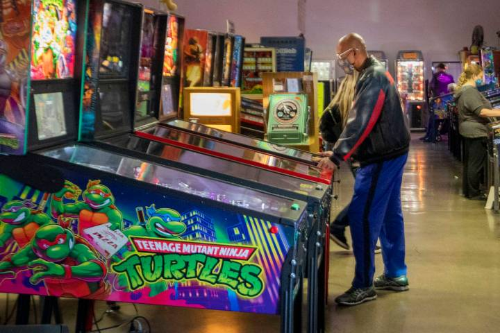 Individuals play pinball during the Pinball Hall of Fame launch of a weekly food truck gatherin ...