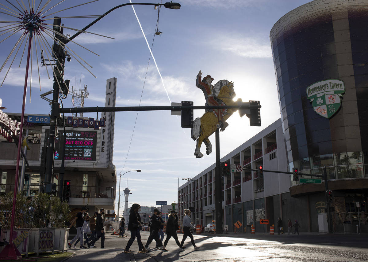 Visitors to downtown cross Fremont Street as temperatures exceeded 70 degrees on Saturday, Jan. ...