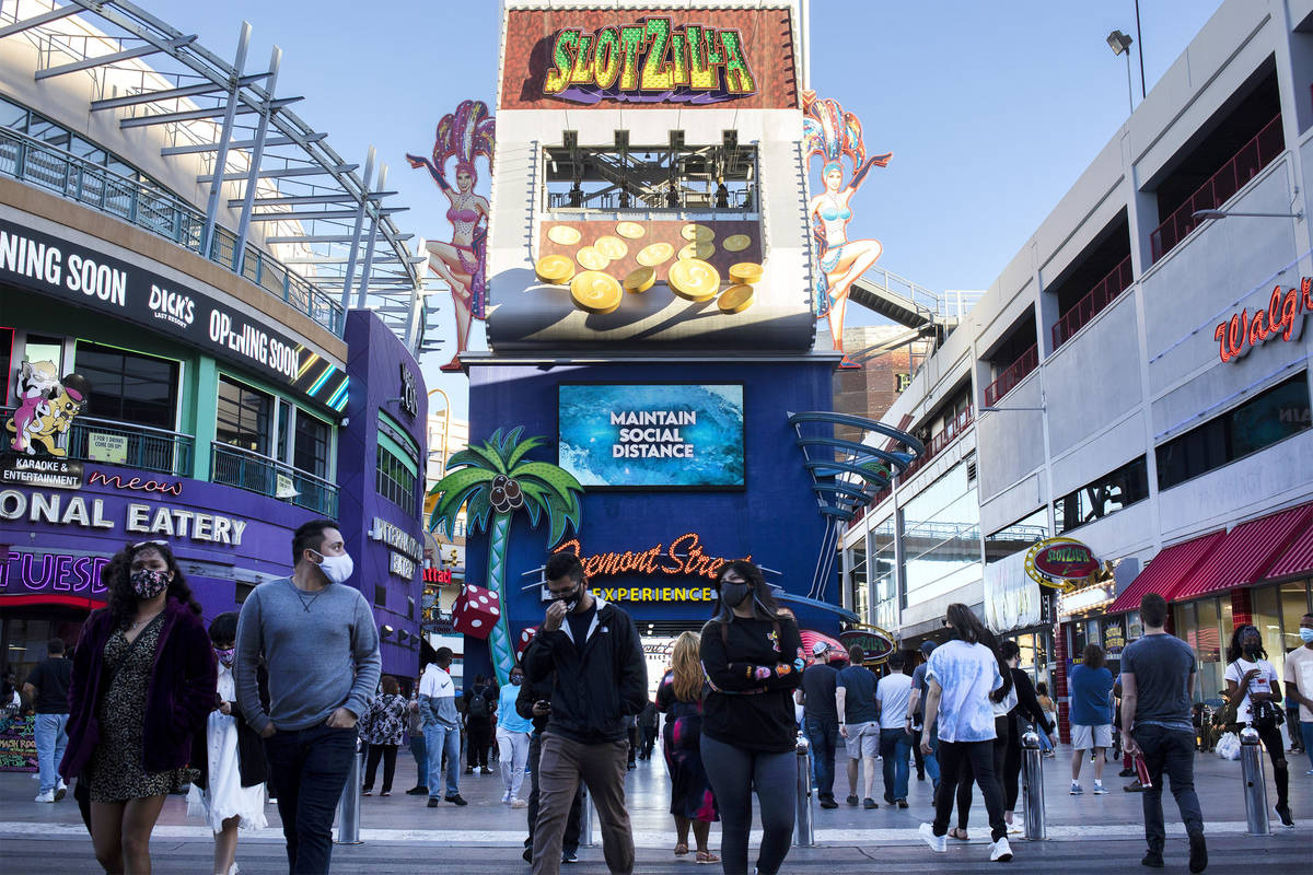 Pedestrians, masked to prevent the spread of coronavirus, roam Fremont Street Experience while ...