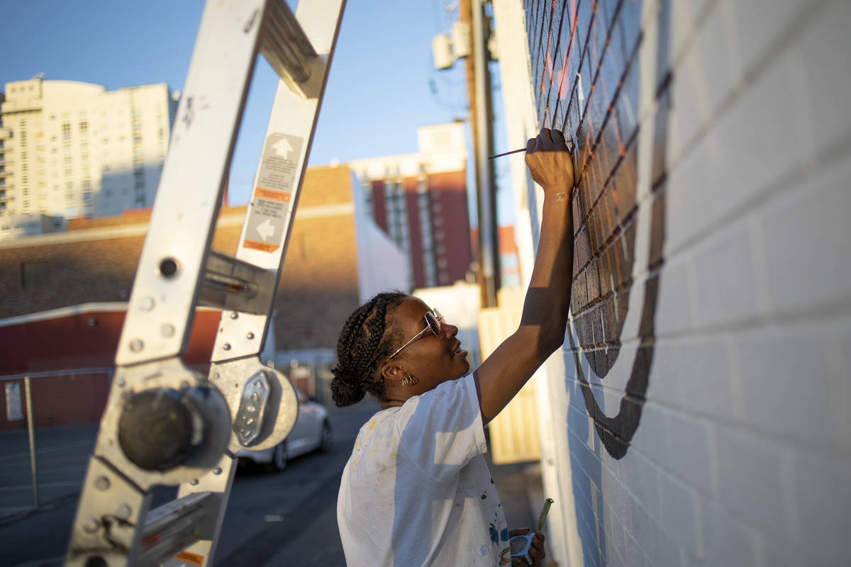 Krystal Rhema, an artist from Los Angeles, paints a mural on the exterior wall of a new, downto ...