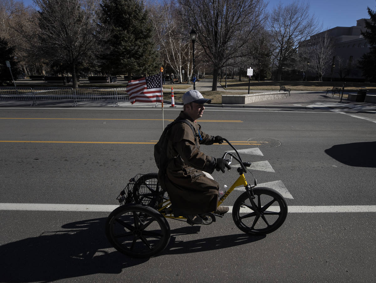 A bicyclist passes by the state Capitol complex on Sunday, Jan. 17, 2021, in Carson City, Nev. ...