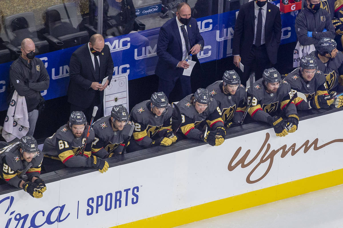 Vegas Golden Knights head coach Pete DeBoer, back center, holds his water bottle as he coaches ...