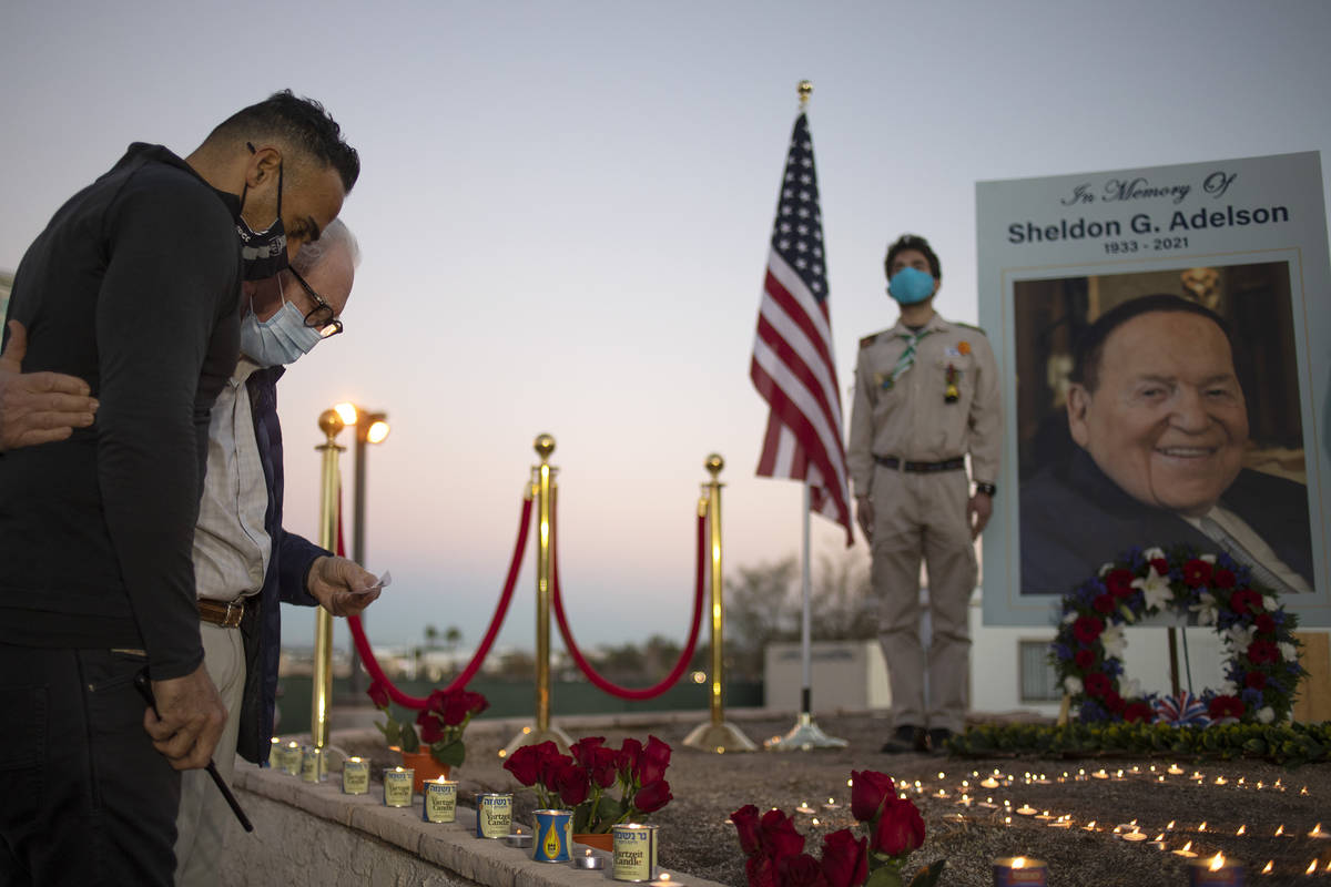 Lior Gal, left, embraces Neville Pokroy as they pay their respects to Sheldon Adelson by lighti ...