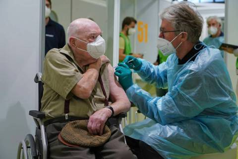 A doctor inoculates Herri Rehfeld, 92, against the new coronavirus with the Pfizer/BioNTech vac ...
