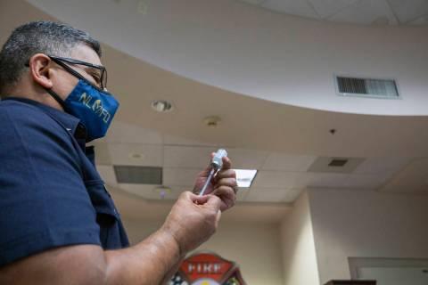 The North Las Vegas Fire Department health care coordinator Fernando Juarez fills a syringe wit ...