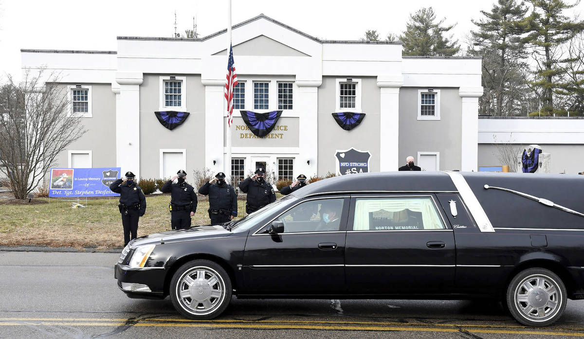FILE - In this Thursday, Jan. 14, 2021. file photo, Norton, Mass. police salute as a hearse car ...