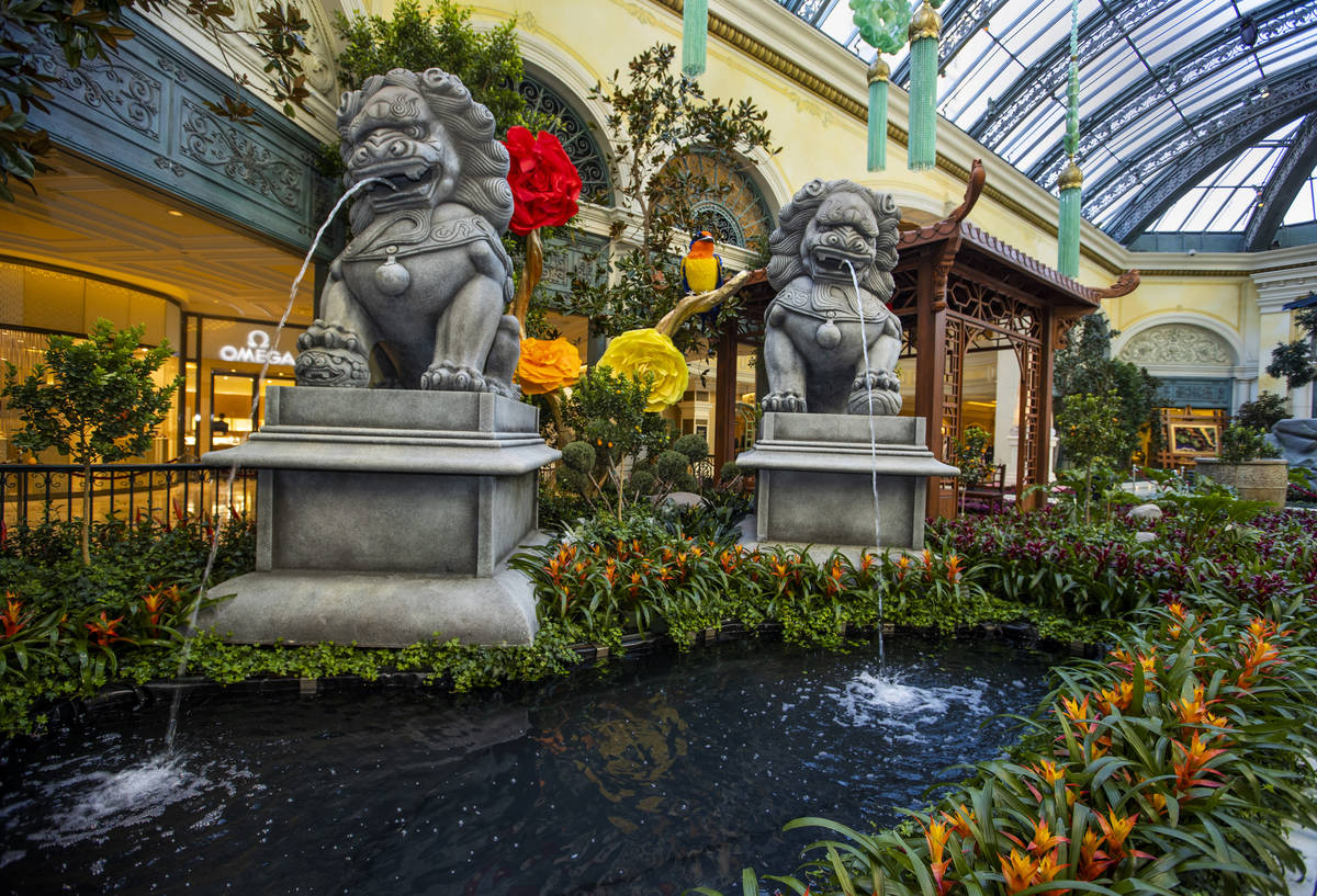 Statues with water coming out of their mouths are surrounded by a variety of flowers as the Bel ...