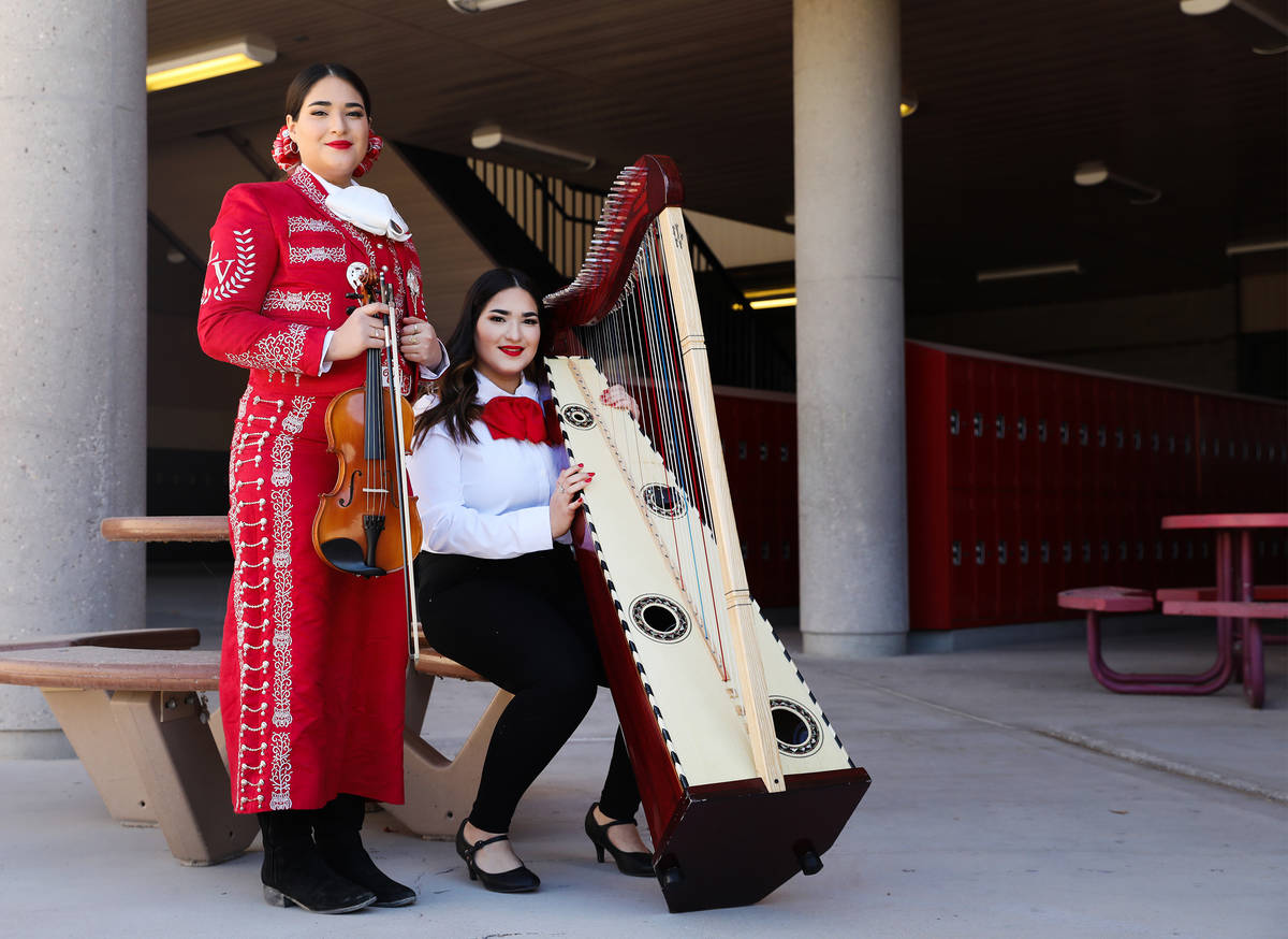 Michelle Madrid, left, who plays the violin, and her twin sister, Rachelle, who plays the harp, ...