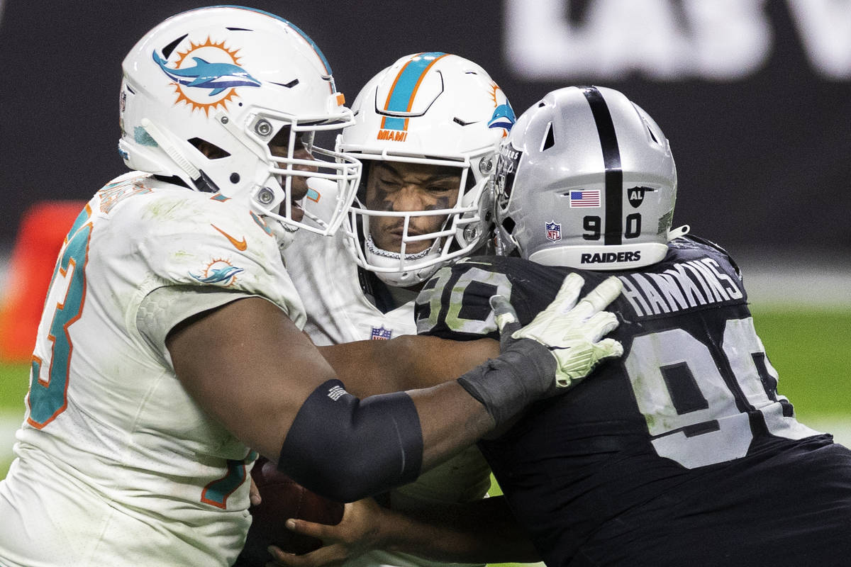 Miami Dolphins quarterback Tua Tagovailoa (1) is sacked by Raiders defensive tackle Johnathan H ...