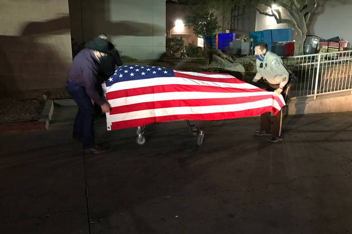 Nye County deputies on Monday, Jan. 18, 2021, drape an American flag over the casket carrying P ...
