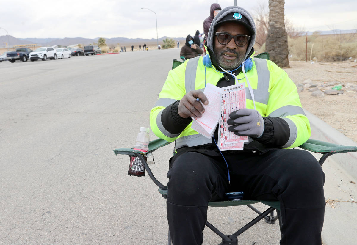 Gary Bradford, 57, of Las Vegas, fills out his tickets while lining up to buy Powerball and Meg ...