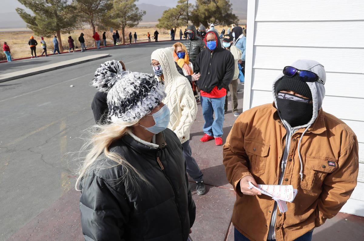 Mario Palencia, right, and Fabiola Herrera, both of Las Vegas, line up to buy Powerball and Meg ...