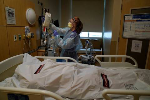 Registered nurse Nikki Hollinger cleans up a room as a body of a COVID-19 victim lies in a body ...