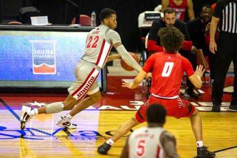 UNLV Rebels guard Nicquel Blake (22) dribbles past New Mexico Lobos guard Isaiah Marin (0) duri ...