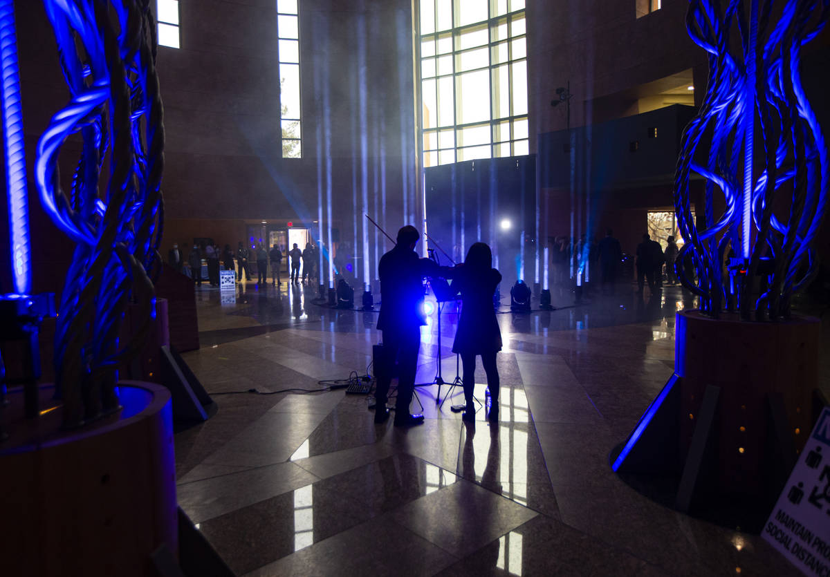 Violinists Dmytro Nehrych, left, and Wonyoung Na perform as 29 lights illuminate the rotunda at ...