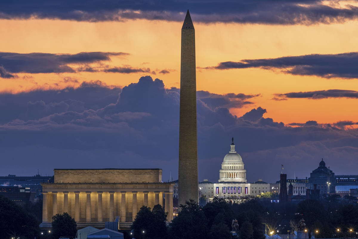 Dawn breaks behind the Lincoln Memorial, Washington Monument, and the U.S. Capitol on Inaugurat ...