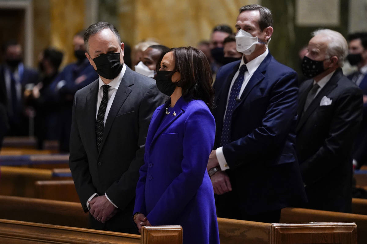 Doug Emhoff looks at his wife Vice President-elect Kamala Harris as they attend Mass at the Cat ...