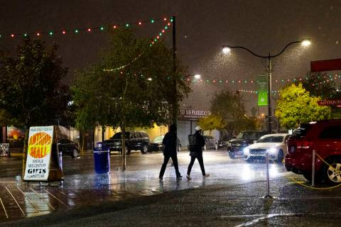 Pedestrians walk through the rain in the Arts District in Las Vegas on Dec. 17, 2020, the first ...