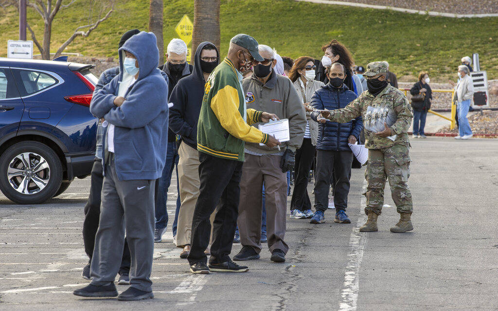 People receive paperwork while waiting in a long line in the parking lot at the Cashman Center ...