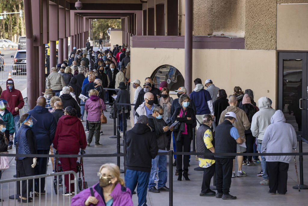 People move along while in line to enter the Cashman Center for COVID-19 vaccinations operated ...