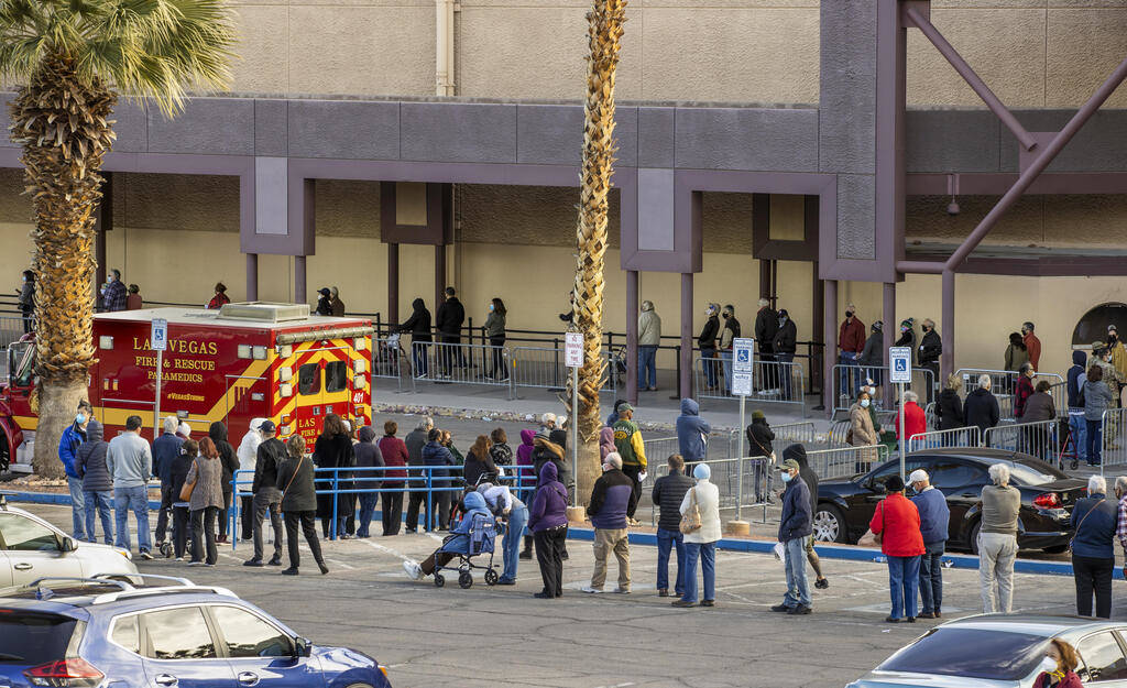 People wait in a long line in the parking lot at the Cashman Center for COVID-19 vaccinations o ...