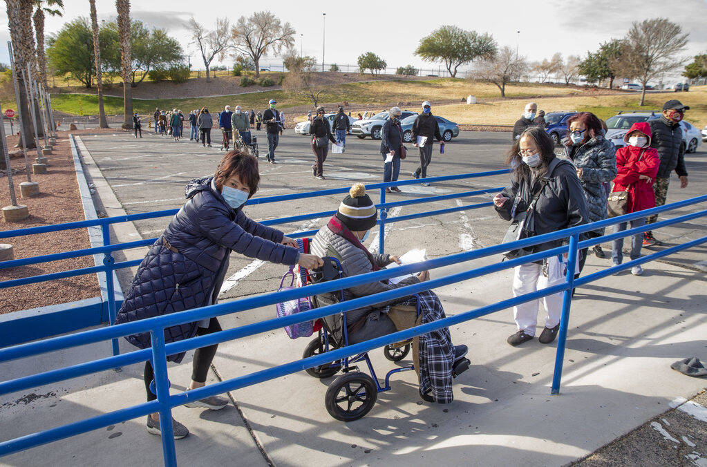 People move along in a long line in the parking lot at the Cashman Center for COVID-19 vaccinat ...