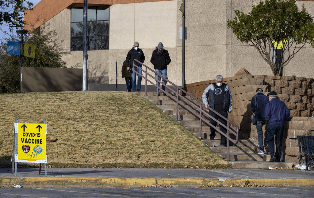 People arrive and depart the Cashman Center for COVID-19 vaccinations operated by the Southern ...
