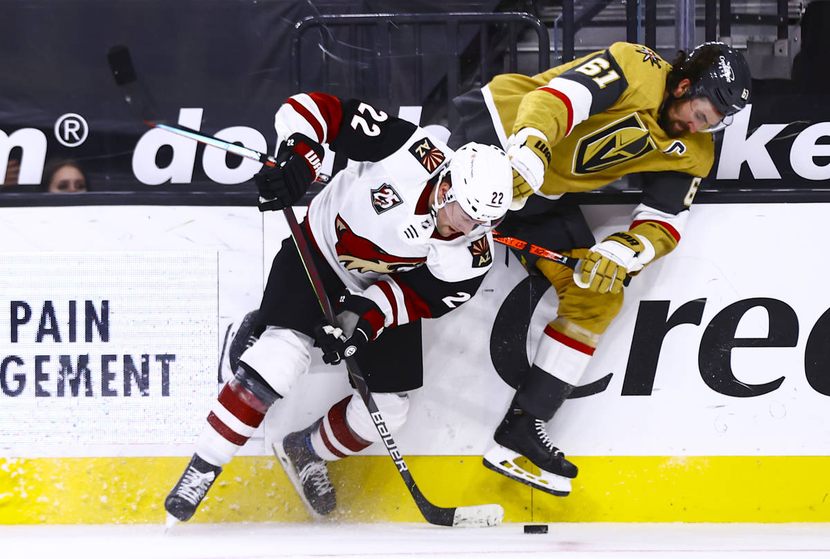 Golden Knights right wing Mark Stone (61) and Arizona Coyotes left wing Johan Larsson (22) batt ...