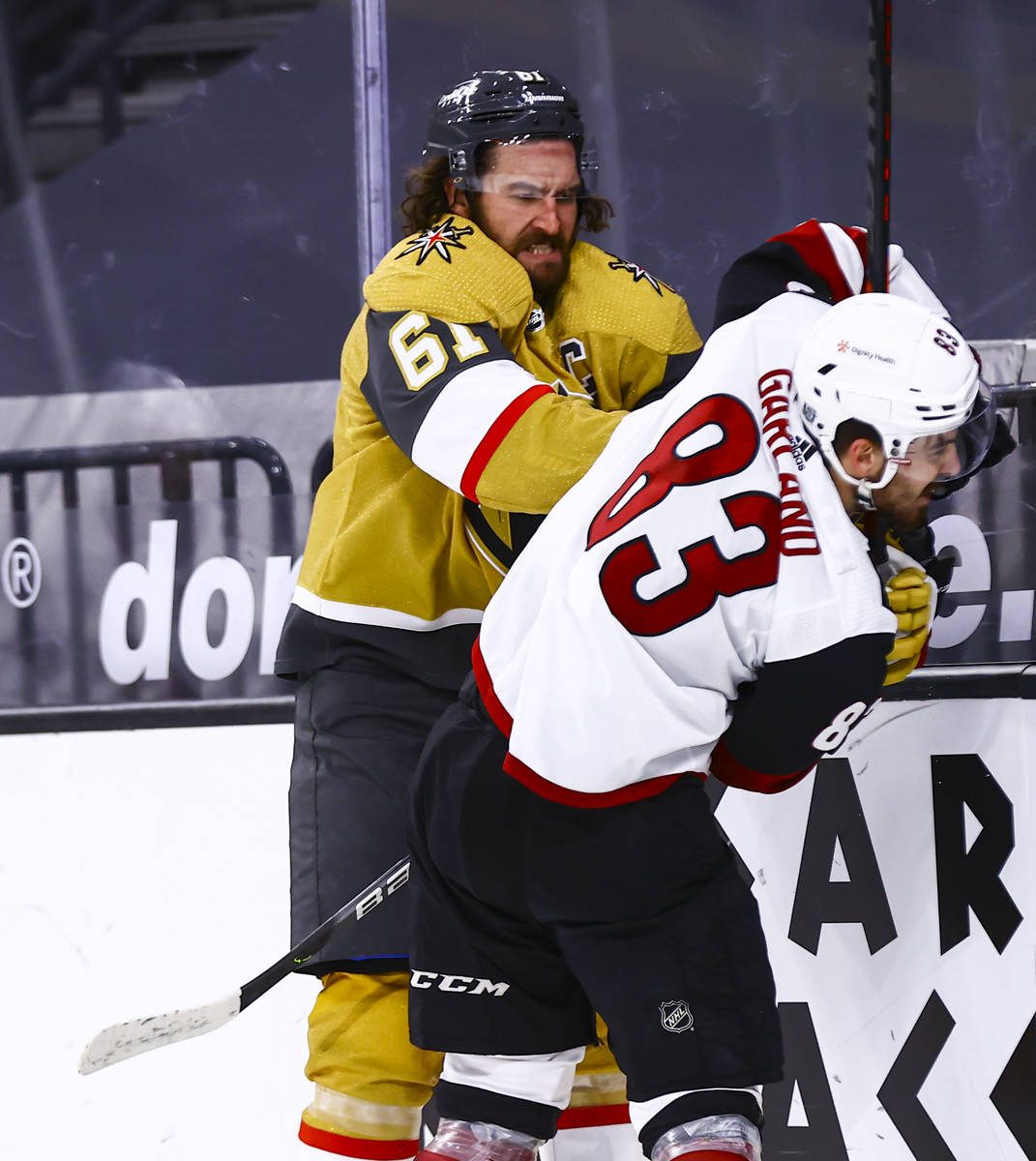 Golden Knights right wing Mark Stone (61) hits Arizona Coyotes right wing Conor Garland (83) du ...