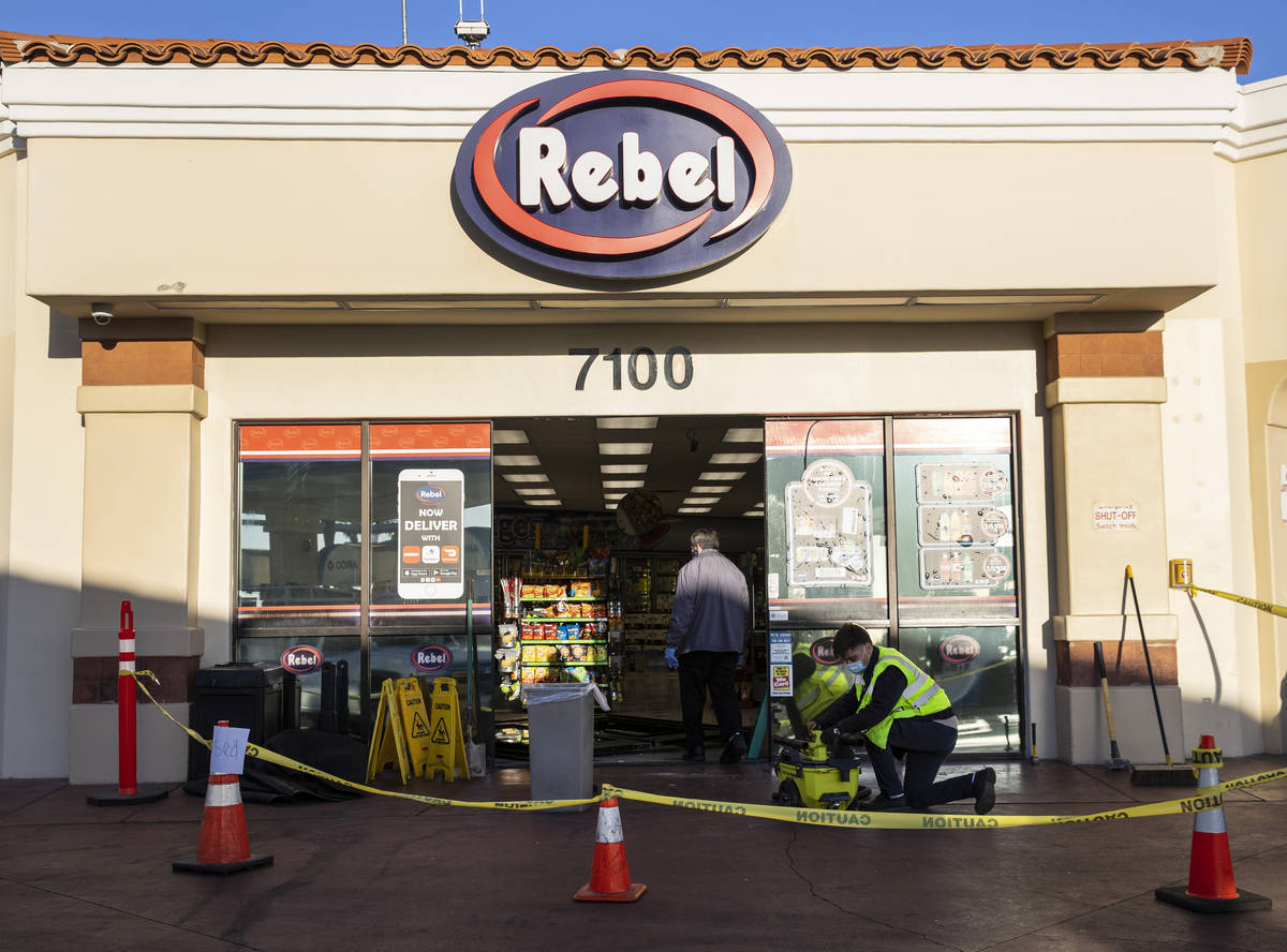 Workers repair damage after a man who got into an argument with a convenience store clerk drove ...