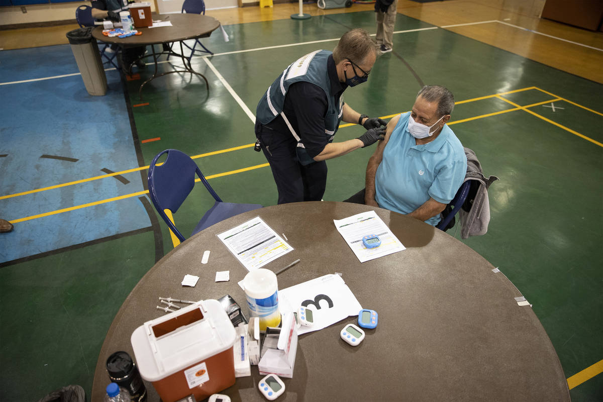 Richard Martinez, 73, right, receives the COVID-19 vaccine from Steve Soderberg, fire engineer ...