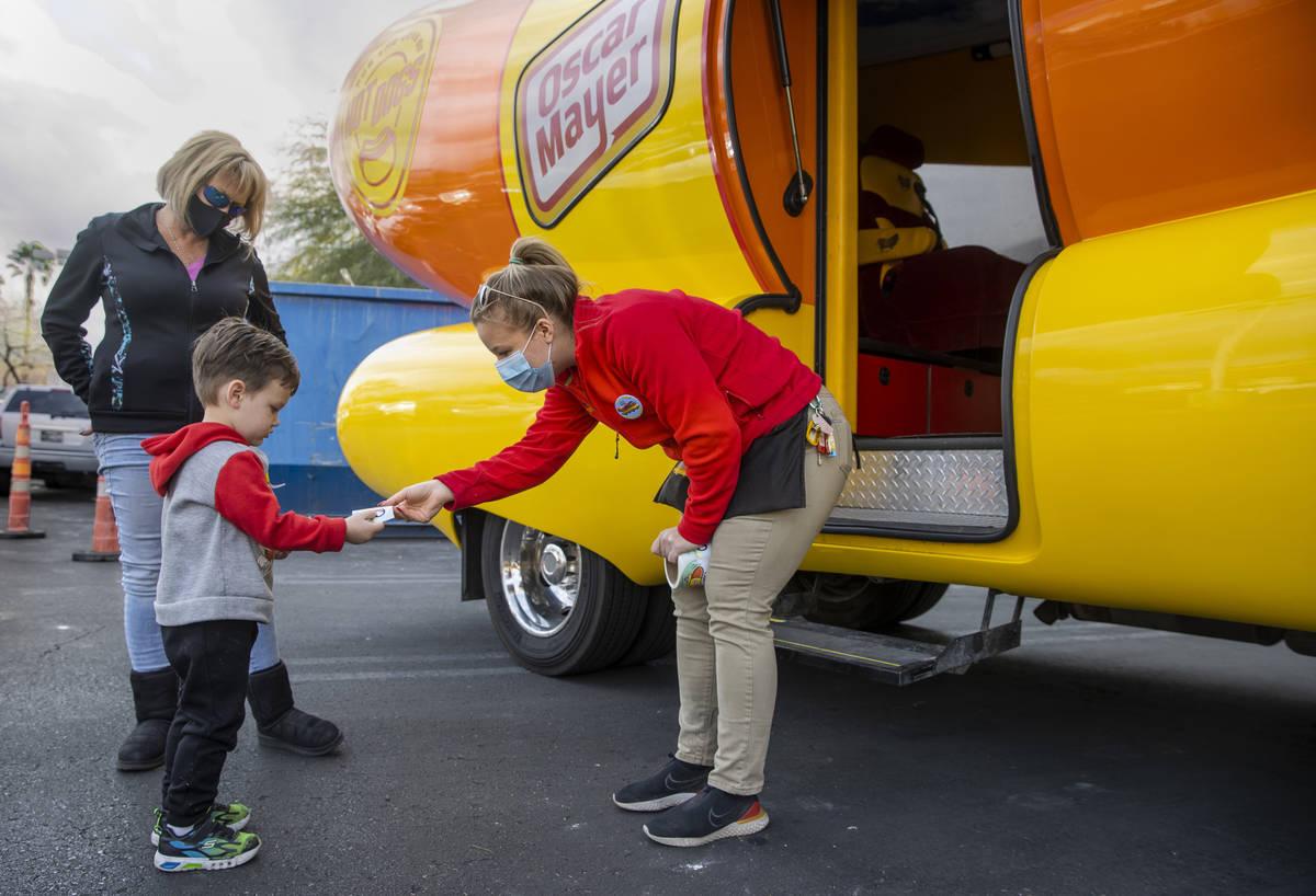 Niener Wiener, right, hands Brenden McCormack, 3, a sticker as he and aunt Corinne Weidman visi ...