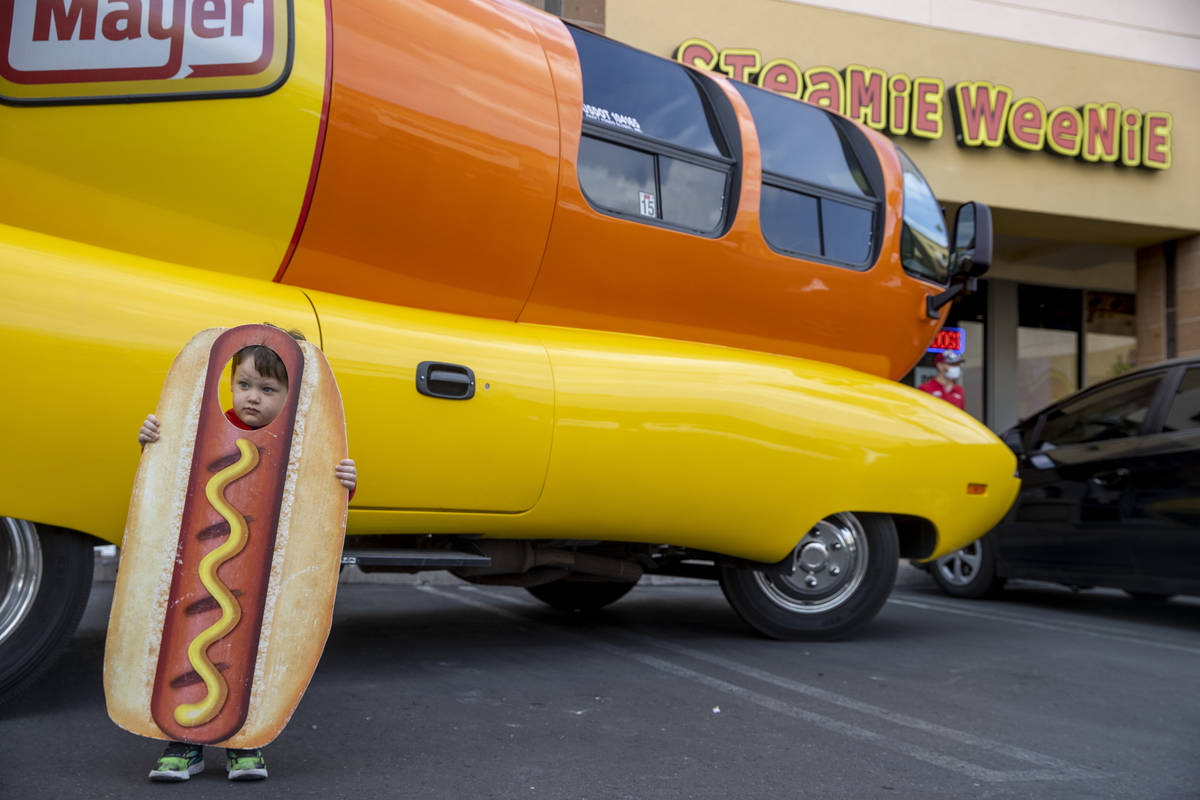 Brenden McCormack, 3, has his picture taken beside the Oscar Mayer Wienermobile parked outside ...