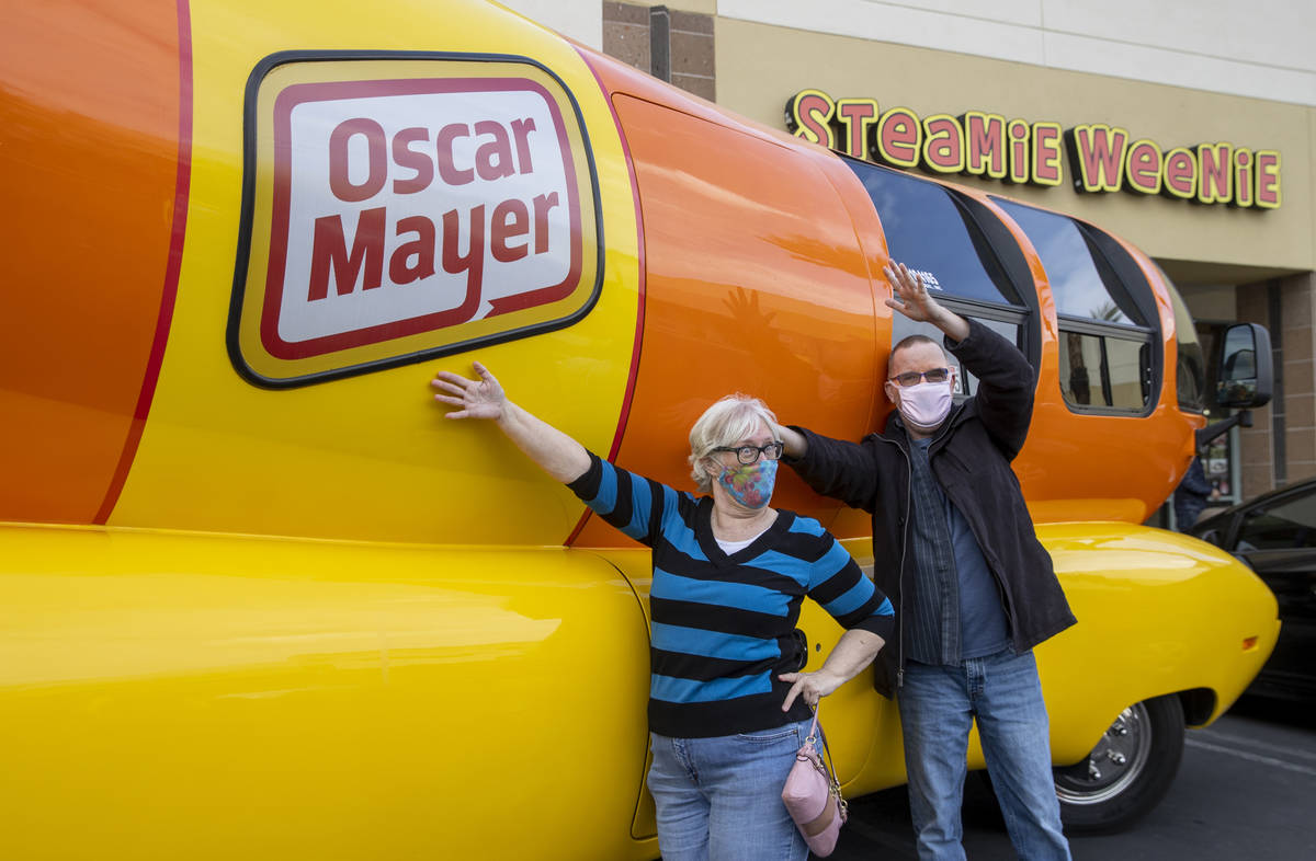 Candy Ochs, left, and Russ Reynolds pose beside the Oscar Mayer Wienermobile parked outside the ...