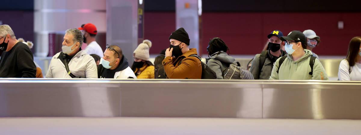 Masked travelers wait to retrieve their luggage in baggage claim Terminal 1 at McCarran Interna ...