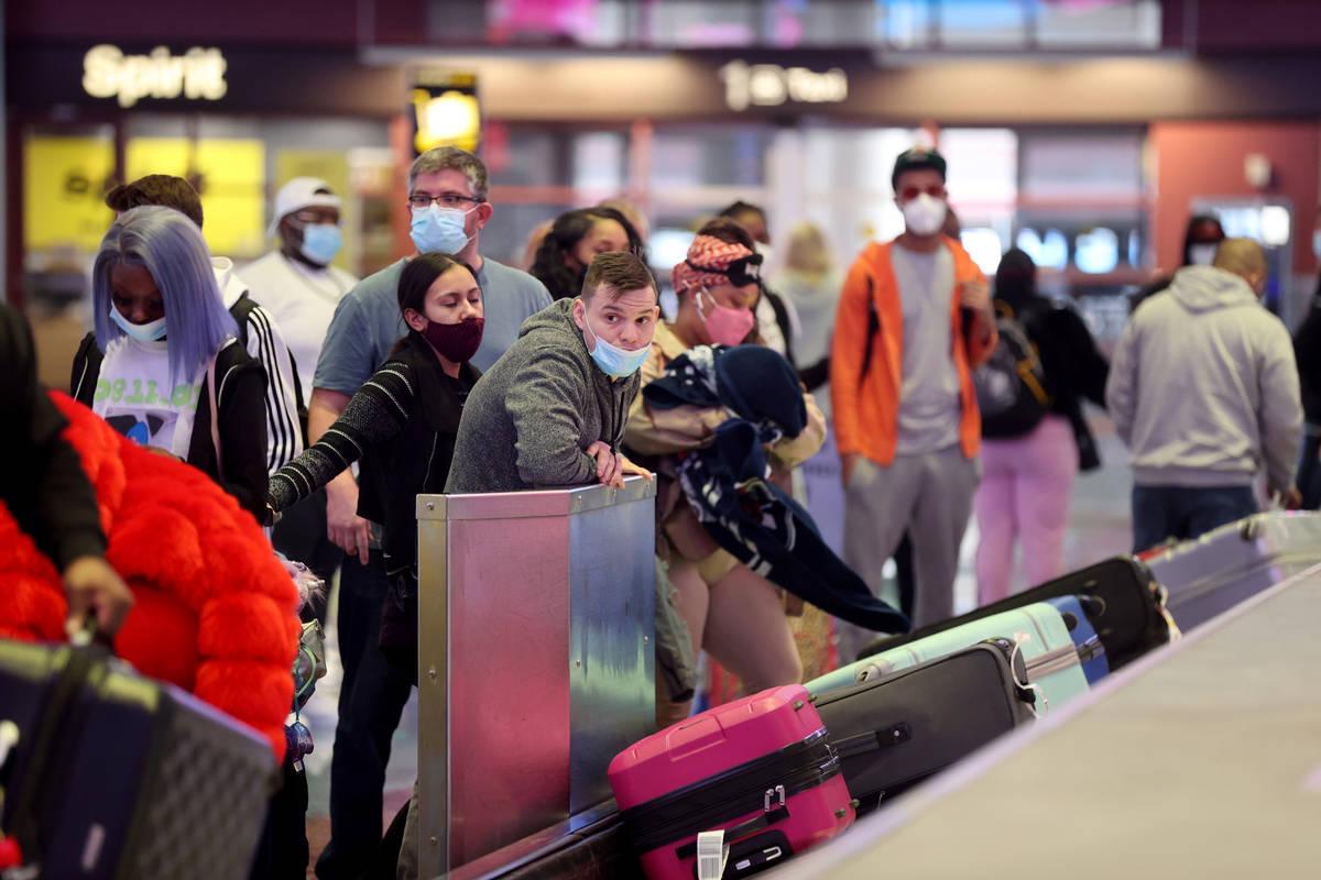 Masked travelers retrieve their luggage in baggage claim Terminal 1 at McCarran International A ...