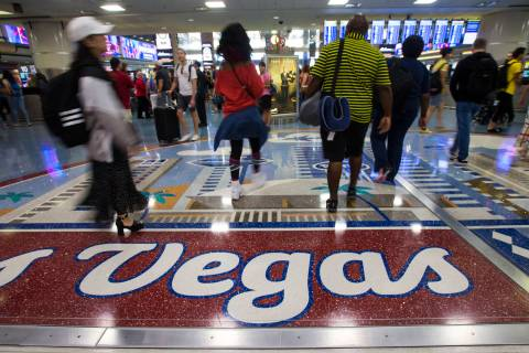 Passengers walk around the baggage claim area at McCarran International Airport ahead of the La ...