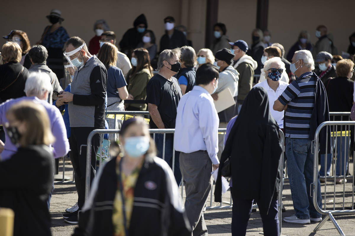 People wait in line to get the COVID-19 vaccine at the Cashman Center in Las Vegas, on Wednesda ...