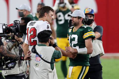 Tampa Bay Buccaneers quarterback Tom Brady, left, shakes hands with Green Bay Packers quarterba ...