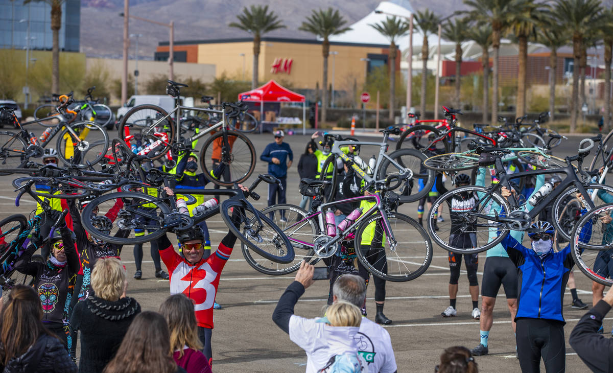 Cyclists hold their bikes over their heads as friends and family gather to honor the five cycli ...