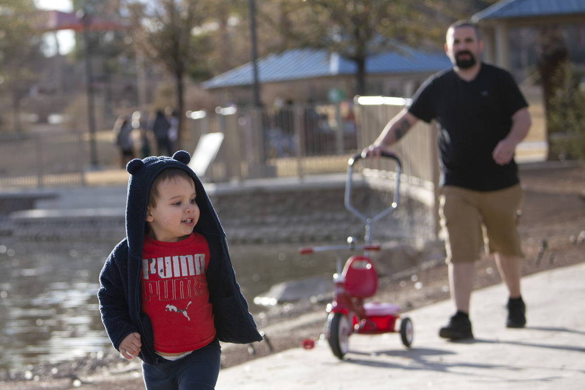 William Dodder, 2, runs around followed by his dad Ryan Dodder at Lorenzi Park on Saturday, Jan ...